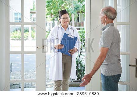 Elderly Man Opening Door To Smiling Doctor Making Visit At Home