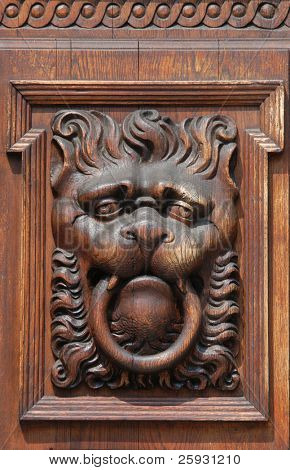 Medieval wooden sculpture of a fabulous monster on the gate of the Old Town Hall in Prague, Czech Republic.