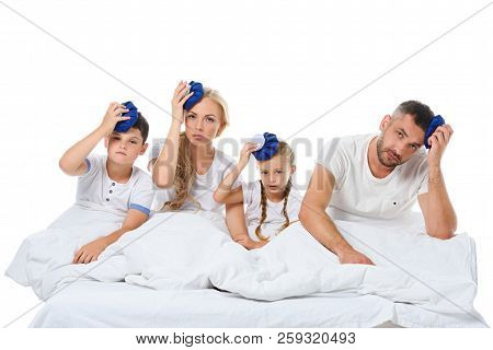 Ill Family Holding Ice Packs On Heads While Sitting In Bed, Isolated On White