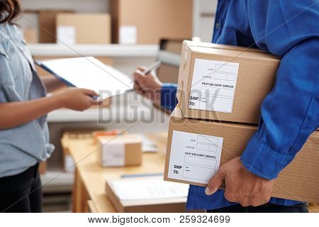 Postman Holding Parcels And Signing For The Delivery At Post Office