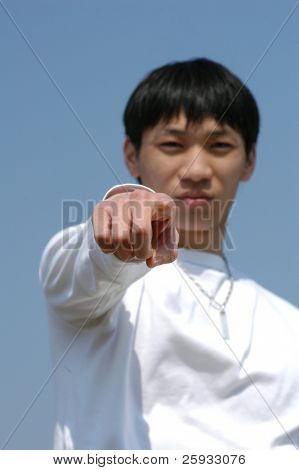 Let's Do It! Young Asian man pointing forward - hand in focus