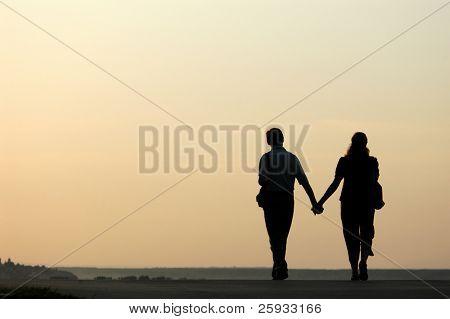 Silhueta amorosa casal caminhando ao pôr do sol