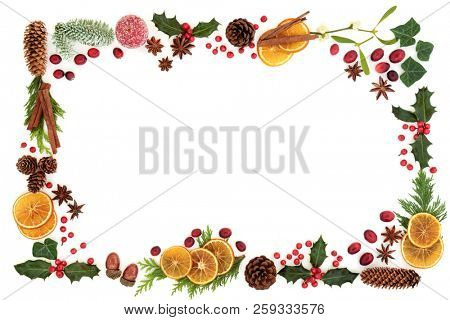 Traditional Christmas and winter flora and food with loose berries forming an abstract background border on white. Gift tag or card for the festive season.
