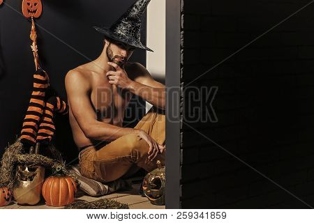 Halloween spirit and supernatural concept. Macho in witch hat and bared torso sitting on floor. Man and pumpkins, stockings, ghost on black wall. Evil spell and magic. Autumn holidays, copy space poster