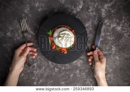 Woman Eating Burrata Cheese On Small Wooden Plate Served With Fresh Tomatoes And Basil On Dark Textu