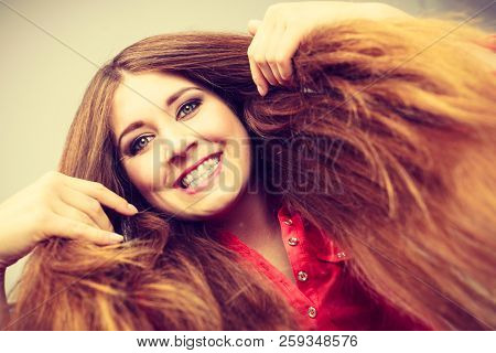 Happy positive woman with long brown hair presenting her healthy hairdo. Haircare concept. poster