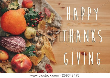 Happy Thanksgiving Text On Pumpkin,vegetables ,colorful Leaves With Acorns And Nuts On Wooden Table.