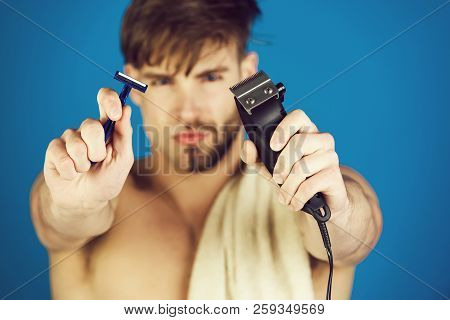 Safety razor and electric shaver or trimmer in hands of blurred handsome man with half shaven face and beard with towel on naked shoulder on blue background. Innovation, archaism. Skincare, grooming poster