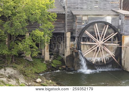 An Old Grist Mill With A Water Wheel.