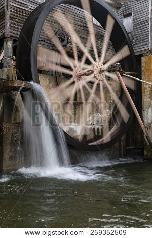 A Water Wheel In Motion At A Grist Mill.