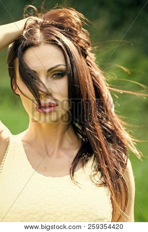 Portrait Of Sensual Attractive Brunette Woman With Bright Makeup In Yellow Dress Touching Hair Looki