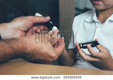 Close Up Of The Hands Of A Doctor Is Helping A Diabetic Child To Use A Lancing Device To Make A Bloo