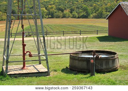 A Windmill Pumping Water Into Wood Water Tank Used On Farms  To Feed Livestock.