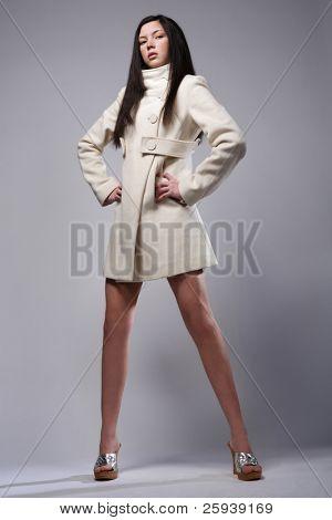 Beautiful fashion model posing in white coat.