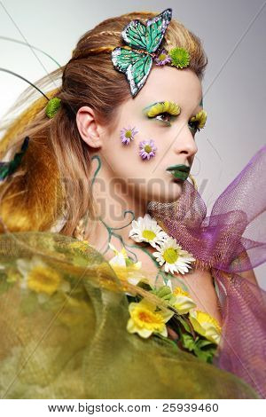 Portrait of beautiful fashion model wearing costume made of flowers.