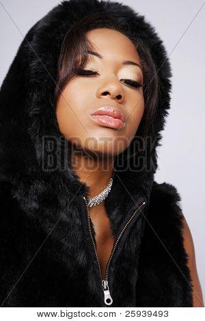 Beautiful young African-American woman in black coat.