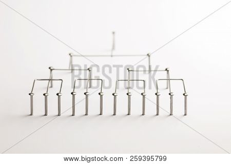 Hierarchy, command chain, company / organization structure or layer concept image. Top down structure made from chrome wires and chrome nails on white. Shallow depth of field. incandescent type light.