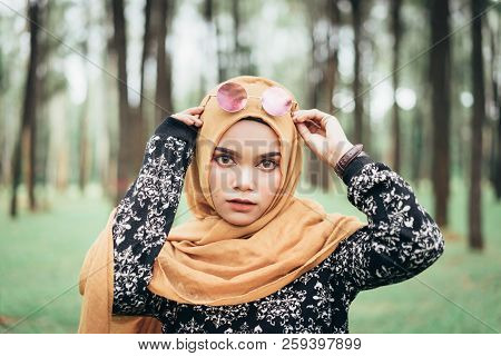 Portrait Of Happy Young Muslim Woman Mellow Yellow Hijab Over Blurred The Pine Forest Background. Vi