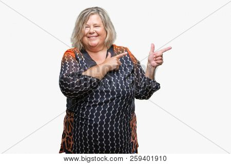 Senior plus size caucasian woman over isolated background smiling and looking at the camera pointing with two hands and fingers to the side.