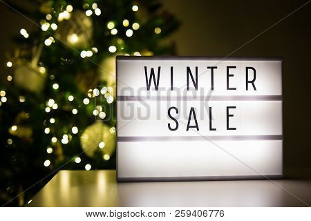 Winter Shopping And Sale Concept - Lihtbox With Winter Sale Text In Dark Room With Decorated Christm