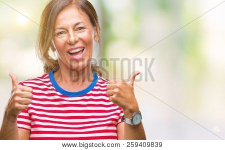 Middle age senior hispanic woman over isolated background success sign doing positive gesture with hand, thumbs up smiling and happy. Looking at the camera with cheerful expression, winner gesture.