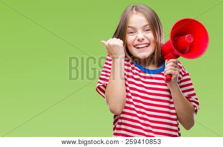 Young beautiful girl yelling through megaphone over isolated background screaming proud and celebrating victory and success very excited, cheering emotion