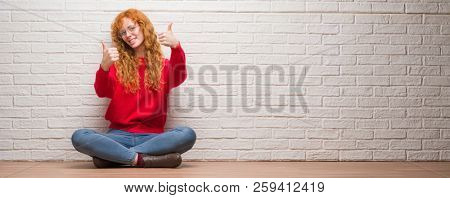 Young redhead woman sitting over brick wall approving doing positive gesture with hand, thumbs up smiling and happy for success. Looking at the camera, winner gesture.