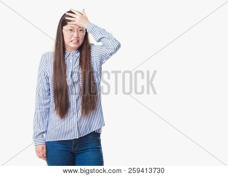 Young Chinese business woman over isolated background wearing glasses stressed with hand on head, shocked with shame and surprise face, angry and frustrated. Fear and upset for mistake.