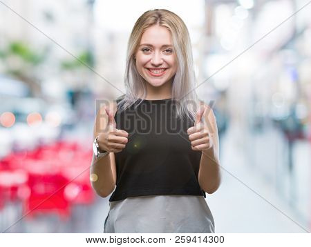 Young blonde woman over isolated background approving doing positive gesture with hand, thumbs up smiling and happy for success. Looking at the camera, winner gesture.