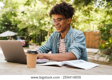 Cheerful young african man student studying at the park with laptop computer