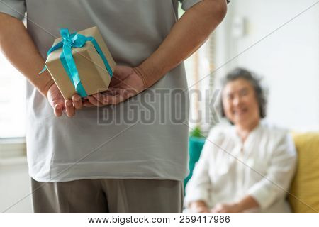 Making A Surprise For Christmas And New Year Concept. Asian Senior Man Hiding Gift Box Behind His Ba