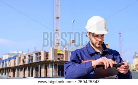 Engineer Protective Helmet Stand In Front Of Blue Sky Background. Contractor Control According To Pl