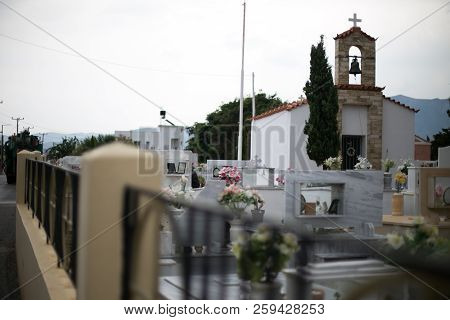 White Cemetery With A Church, A Fence With Black Whips, A Part Of The City Is Dull