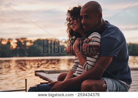 Romantic Couple. Happy Young Couple Embracing And Smiling While Sitting On The Pier Near The Lake