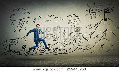 Businessman In Suit Running Life Quest With Obstacles. Self Overcome Climbing Mountain With Ups And