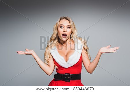 Surprised Beautiful Woman In Santa Dress Doing Shrug Gesture Isolated On Grey Background