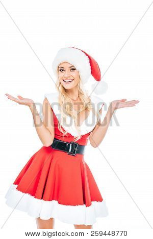Smiling Woman In Santa Dress And Christmas Hat Doing Shrug Gesture Isolated On White Background