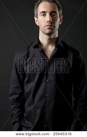Handsome man posing in black shirt on dark background in studio.