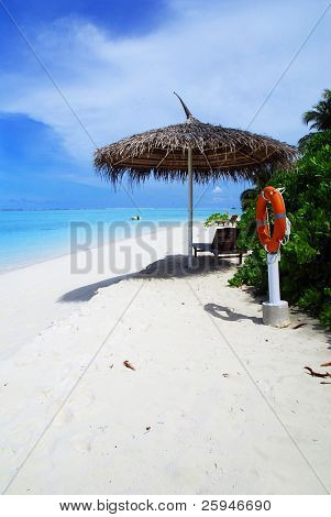 Beautiful tropical beach with old umbrella and lifebuoy
