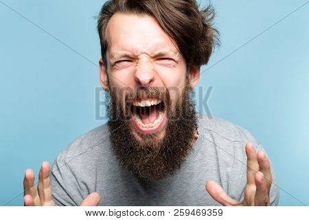 anger and fury. emotional breakdown. enraged man screaming. portrait of a young bearded guy on blue background. facial expression and feelings concept. poster