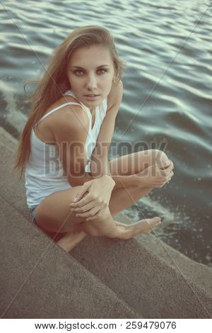 Portrait Of Pretty Young Woman In White T-shirt, Sitting On The Pier, Steps In An Erotic Pose Agains