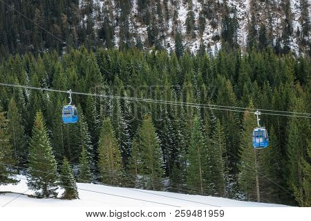 Alpine Transportation Vehicles On Cableway, Traveling Over Snowy Fir Trees, Through The Alps Mountai