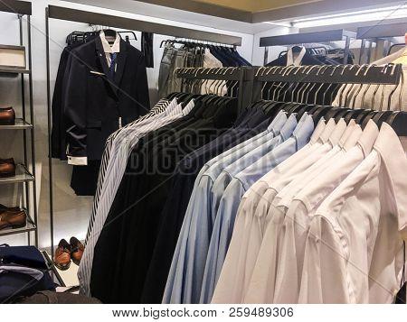 Set of man suit , striped Shirts ,shoes,,handbag on hangers at shop