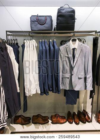 Set of man suit , Shirts ,shoes,,handbag on hangers at shop