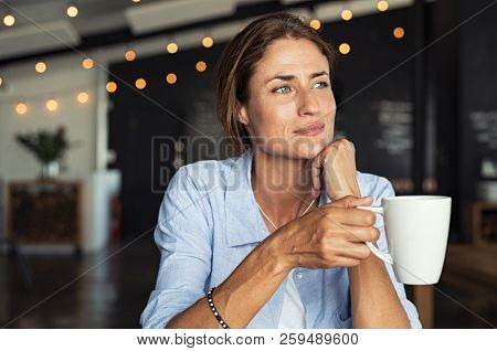 Thoughtful mature woman sitting in cafeteria holding coffee mug while looking away. Middle aged woman drinking tea while thinking. Relaxing and thinking while drinking coffee.