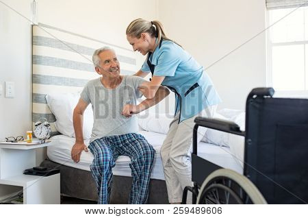 Smiling nurse assisting senior man to get up from bed. Caring nurse supporting patient while getting up from bed and move towards wheelchair at home. Helping elderly disabled man standing up.