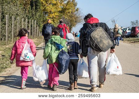 Berkasovo, Serbia - October 31, 2015: Refugees Walking Carrying Heavy Bags On The Croatia Serbia Bor