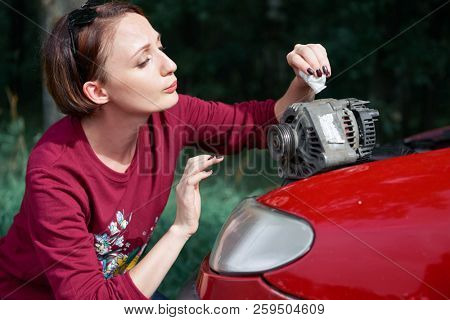 a young girl stands at a broken car and holds a bad spare part, an electric generator, does not understand how to repair, clean it with a cloth