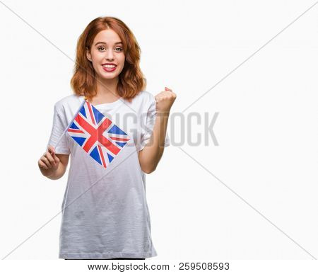 Young beautiful woman holding flag of united kingdom over isolated background screaming proud and celebrating victory and success very excited, cheering emotion