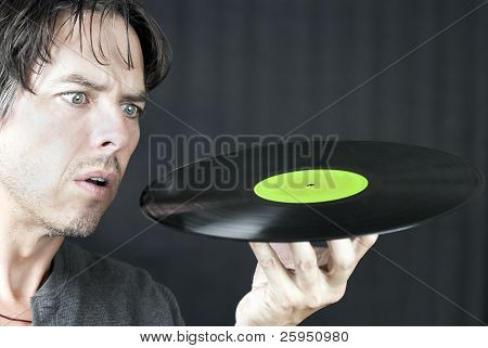 Close-up of a man looking at a LP in confusion. poster